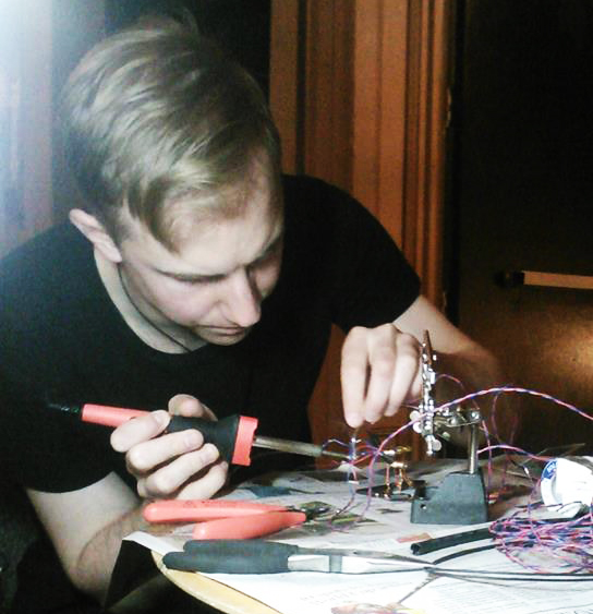 Kyle soldering cables before the show